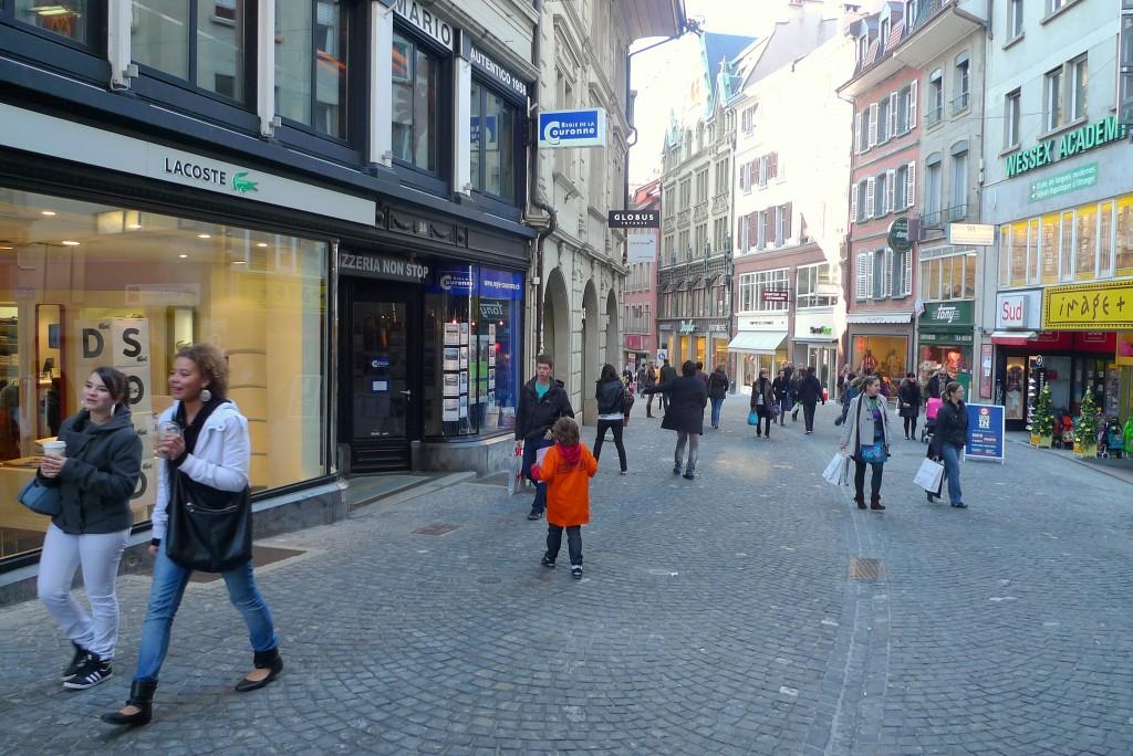 Пешеходы на Rue de Bourg одеты легко.